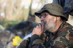 Old homeless man smoke a cigarette. Dirty homeless man smoke a cigarette Royalty Free Stock Photo