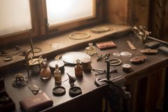 Old horology or watchmakers laboratory. With a wooden work bench spread with hand tools in front of a window Royalty Free Stock Image