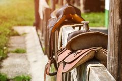 Old horse saddle placed on wooden fence next to house, lit by su stock image