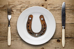 Old horseshoe on plate, fork and knife Stock Photos
