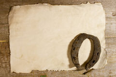 Old horseshoe and a sheet of paper Stock Photos