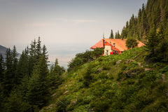 Old hostel building with red roof in the mountains of Romania.  stock photo