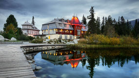 Old Hotel. Illuminated old hotel on the shores of a mountain lake in the evening stock photo