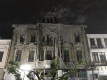 Old spooky ruin hotel in the night and a spooky tree in front. Old hotel spooky in the night old architecture many windows and a spooky tree in front royalty free stock images