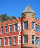 Old hotel with tower. An old red brick hotel with a tower with blue sky in the background Stock Photos