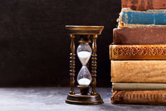 Old hourglass with books stock photography