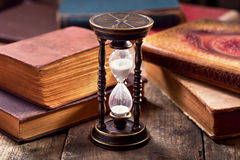 Old hourglass with books. On wooden background Royalty Free Stock Images