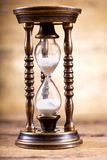 Old hourglass on a wooden background. Close up of old hourglass on a wooden background royalty free stock photos