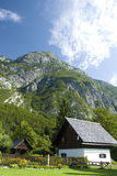 Old house. A cottage in Ukanc at lake Bohinj in Slovenia with mountain in clear weather in background Royalty Free Stock Photos