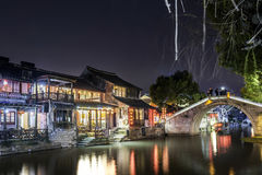 Old house along the river and Huanxiu bridge at night stock images