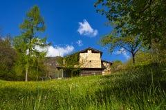 Old house in an alpine prairie. An olf house in an alpine prairie in the italian alps stock images