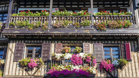 An old house with a balcony decorated with flowers Stock Photo