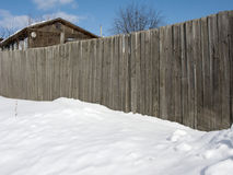 Old house behind the high wooden fence in winter. View of high wooden fence with old house behind on sunny winter day Stock Photo