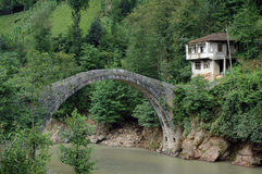 Old house and bridge. An old house in the forest with its own arched stone bridge to cross the river Royalty Free Stock Photo