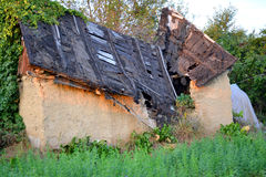 Old house with the broken roof and overgrown grass Stock Photo