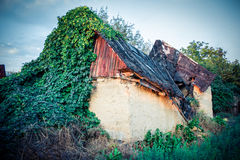 Old house with the broken roof and overgrown grass Royalty Free Stock Photo