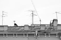 Old house with chimneys and television antennas. Part of the old house with chimneys and with television antennas on a roof in monochrome tone royalty free stock images