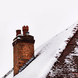 Old house clay brick chimney in winter covered with snow Stock Images