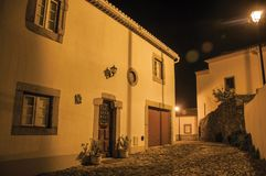 Old house in cobblestone alley at dusk in Marvao. Charming facade of old house with whitewashed wall and wooden ornate door in cobblestone alley, at dusk in royalty free stock images