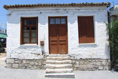 Old house in Corinth. A closeup of the front of a small old house, painted in white and made from stones. In Corinth, Greece Royalty Free Stock Photos