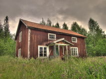 Old house in countryside. Exterior of old wooden house in countryside with forest and dark clouds in background Royalty Free Stock Photo