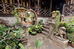 Old house courtyard in village of Thailand, with big mirror, stone steps and traditional statues Royalty Free Stock Images
