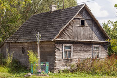 Old house and cross in front of building in Aleksicze Poland Stock Photo