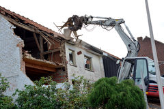 An old house is demolished with an excavator Royalty Free Stock Image