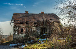 Old house. In dilapidated condition with broken windows blue sky and fog in the background Royalty Free Stock Photos