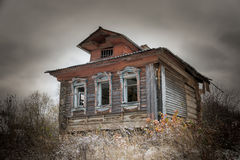The old house. Old dilapidated wooden one-story house, standing alone in the tall grass Royalty Free Stock Image