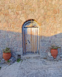 Old house door and flowerpots. Between light and shadow Stock Photography