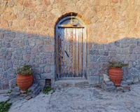 Old house door and flowerpots. Between light and shadow Royalty Free Stock Image