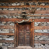 Old house door, wall decorated with horns. Nakthan, Parvati valley, Himachal Pradesh, India stock images