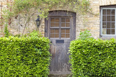 Old house doors in english traditional stone cottage. Old brown wooden door in traditional honey comb stone cottage with green beech hedge in front, in rural Royalty Free Stock Image