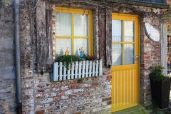 An old house in Durbuy, Belgium. An old house with yellow window and front door in Durbuy, Belgium. Durbuy is a Walloon city and municipality located in the Stock Images