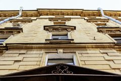 Old house in europe.  cracks on the facade and decorated with stucco. Bottom view of old house in european city cracks on the facade and decorated with stucco stock photos