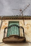 Old house facade with rusty balcony and green blind stock photo