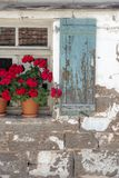 Old house facade. Section from an old house facade with beautiful red flowers on the window pill against the aged window shutters and the peeled wall stock images