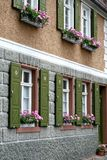 Old house facade with shutters and flowers. Royalty Free Stock Images