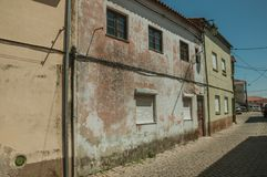 Old house facade with worn paint on plaster wall. And deserted alley, in a sunny day at Belmonte. A cute small town, birthplace of the navigator Pedro Alvares royalty free stock photo