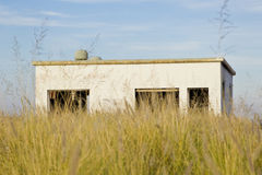 Old house in a field of dry grass Stock Image