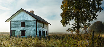 Old house in a field in morning light. Old, abandoned house in a field in morning light with grown grass in foreground and morning fog in the background Stock Photos