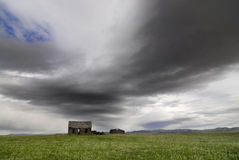 Old House in Field with Storm Clouds Stock Images
