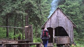 The old house of the forester in the forest, the smoke comes from the chimney, a Caucasian male tourist with walking