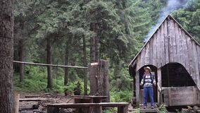 The old house of the forester in the forest, smoke comes from the chimney, a Caucasian male tourist with walking sticks
