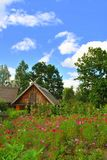 The old house in the garden. The rustic old  wooden house in the flower garden Royalty Free Stock Image