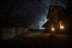 Old house with a Ghost in the forest at night or Abandoned Haunted Horror House in fog. Old mystic building in dead tree forest. royalty free stock photography