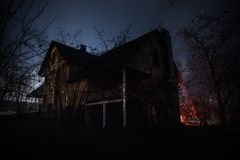 Old house with a Ghost in the forest at night or Abandoned Haunted Horror House in fog. Old mystic building in dead tree forest. stock images