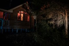 Old house with a Ghost in the forest at night or Abandoned Haunted Horror House in fog. Old mystic building in dead tree forest.
