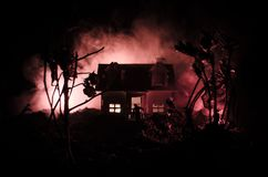 Old house with a Ghost in the moonlit night or Abandoned Haunted Horror House in fog. Old mystic villa with surreal big full moon. Royalty Free Stock Images